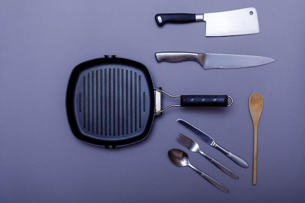 Coltelli in metallo con il nero su un tavolo grigio, griglia, asciugamano. disposizione piana, disposizione.