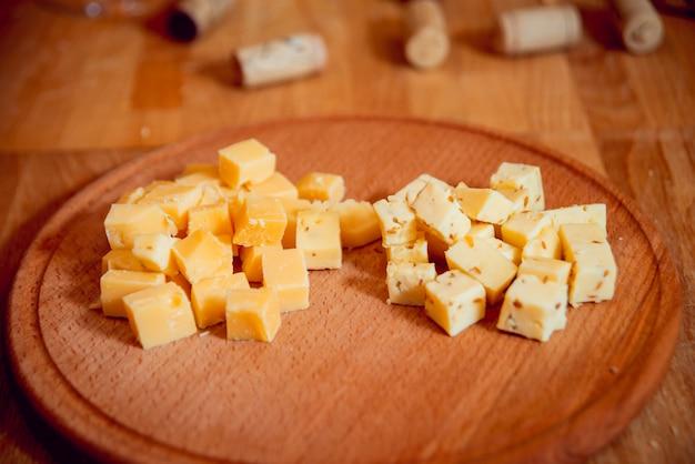 Coltello con pezzo di formaggio su un tavolo scuro