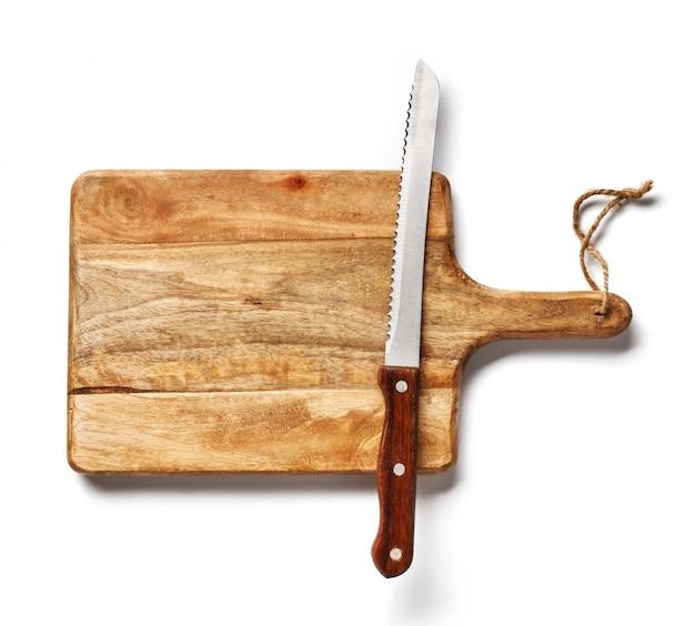 Coltello da pane d'annata sul bordo di legno isolato