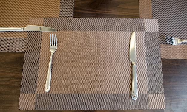 Coltello da tavola e forchetta con tovaglia sul tavolo di legno