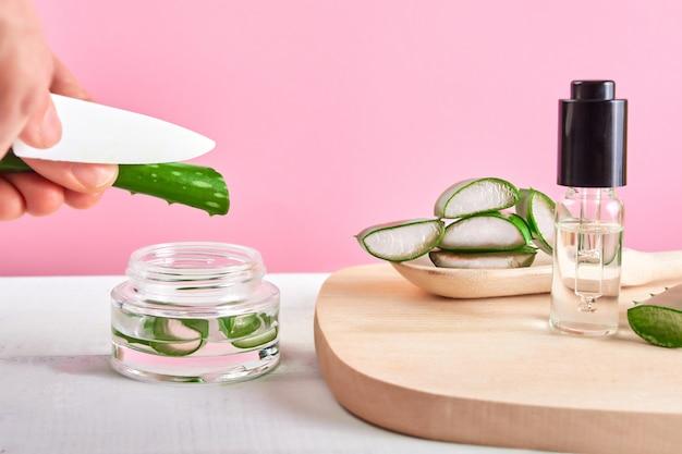 Coltello della tenuta della mano che taglia aloe vera verde. piatto di legno con pezzi di aloe su sfondo