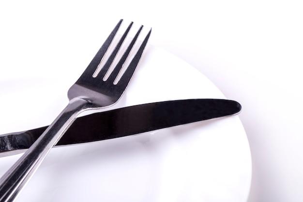 Coltello e forcella sul piatto vuoto su un bianco