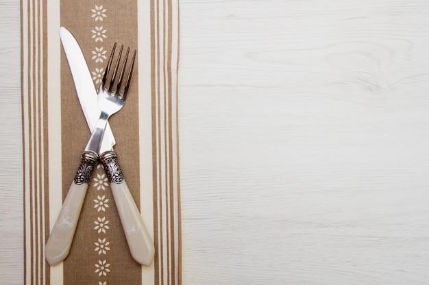 Coltello e forchetta al tovagliolo su legno bianco