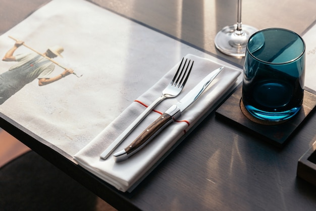 Coltello e forchetta con tovagliolo sul tavolo in legno per una cucina raffinata