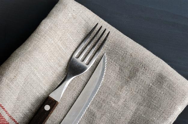 Coltello e forchetta sulla tovaglia di lino