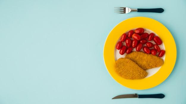 Coltello, forchetta e piatto con petto di pollo e pomodoro sulla scrivania blu