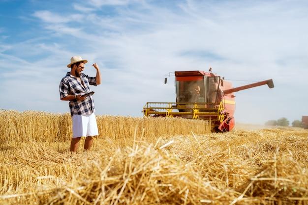 Coltivatore allegro che sta davanti alla mietitrebbiatrice rossa funzionante che celebra un buon raccolto.