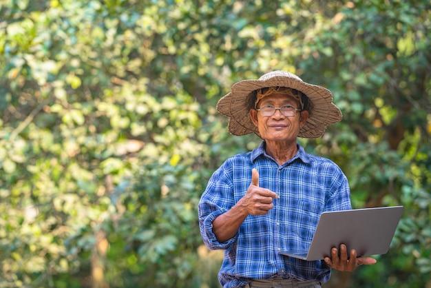 Coltivatore asiatico con il concetto di smartphone e laptop, business e tecnologia