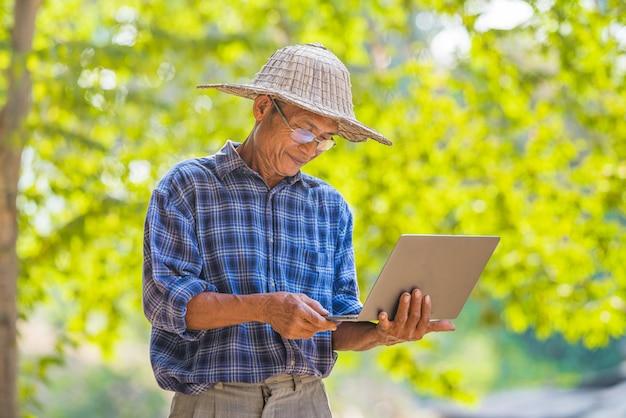 Coltivatore asiatico dell'uomo con il concetto di affari e di tecnologia del computer portatile e dello smart phone, agricoltore asiatico dell'uomo sullo spazio vuoto della copia