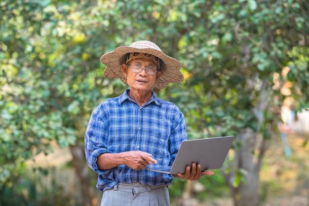 Coltivatore asiatico dell'uomo con il concetto di affari e tecnologia del computer portatile e dello smart phone