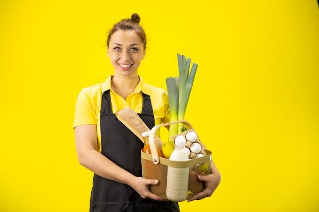 Coltivatore attraente sorridente nel canestro uniforme della tenuta con i prodotti di fattoria della drogheria