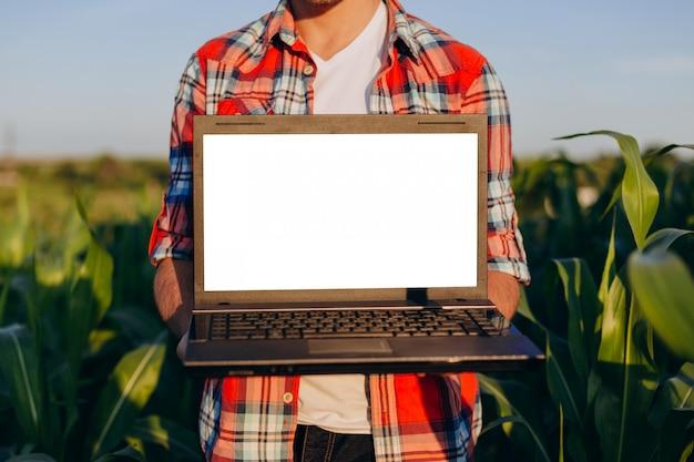 Coltivatore che sta in un computer portatile aperto della tenuta del campo. mockup schermo bianco