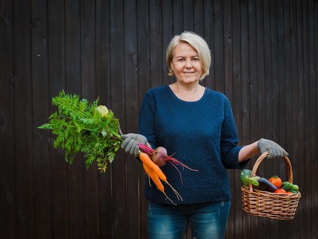 Coltivatore che tiene un cestino con le verdure organiche