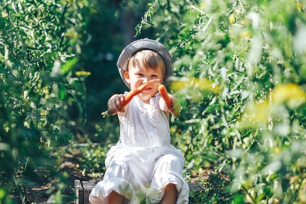Coltivatore di bambino con carote e clother cacual seduto nell'erba verde