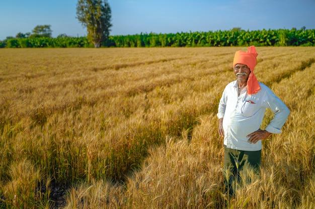 Coltivatore indiano rurale felice nel campo agricolo