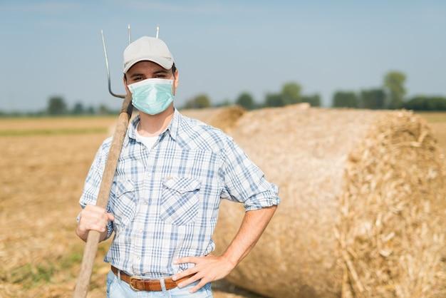 Coltivatore nel suo campo mentre indossa una maschera, concetto di pandemia di coronavirus
