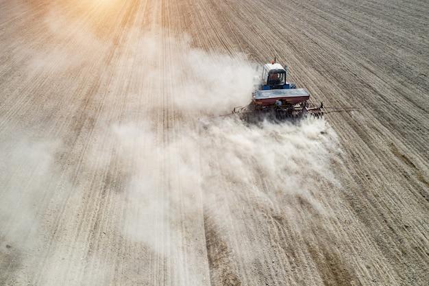 Coltivatore semina, semina colture in campo. la semina è il processo di semina nel terreno come parte delle attività agricole all'inizio della primavera.