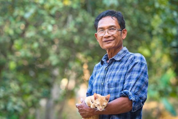 Coltivatore senior dell'uomo asiatico con il gatto, agricoltore asiatico dell'uomo sullo spazio vuoto della copia