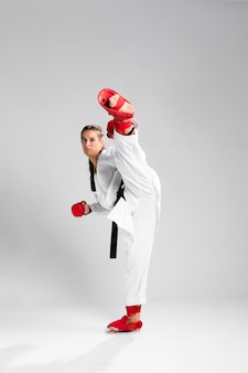 Combattente della ragazza con i guanti della scatola su fondo bianco