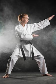 Combattente di arti marziali che posa colpo pieno