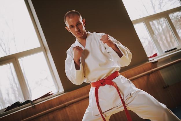Combattente di arti marziali del forte uomo in mosse bianche di addestramento.