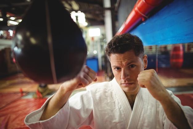 Combattente di karate praticando karate con sacco da boxe