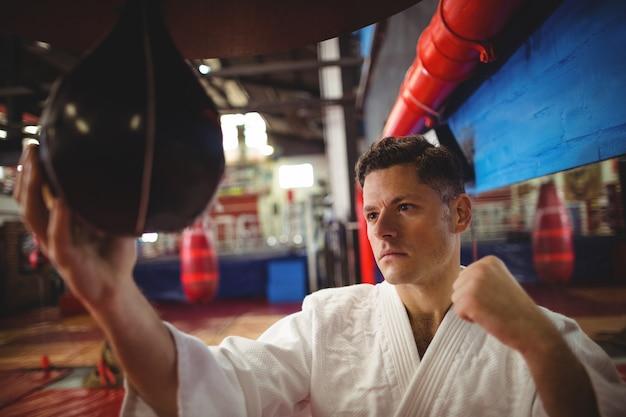 Combattente di karate praticando karate con speed bag