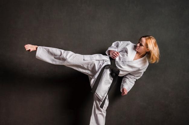 Combattente femminile di karatè che dà dei calci alla vista frontale