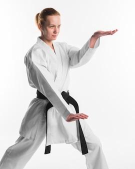 Combattente femminile di karatè che posa colpo medio