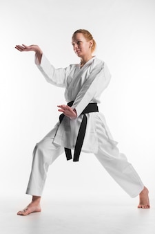 Combattente femminile di karatè che posa colpo pieno