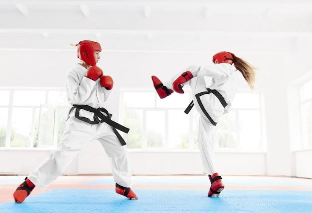 Combattente femminile due che pratica calcio e pugno di karatè.