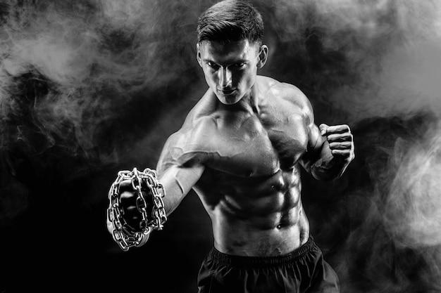 Combattente muscolare serio che fa il pugno con le catene intrecciate sul suo pugno.