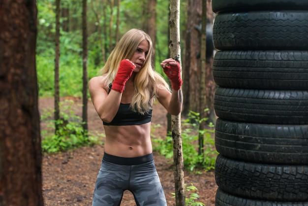 Combattente professionista del pugile della donna che posa nella posizione di pugilato, risolvente all'aperto.