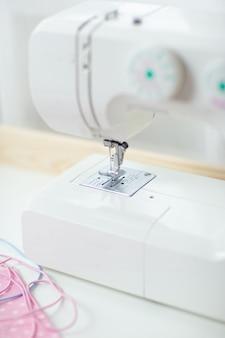 Come cucire la maschera facciale, il processo di cucitura della maschera protettiva, pezzi di stoffa punteggiata, fili e macchina da cucire sul tavolo bianco.