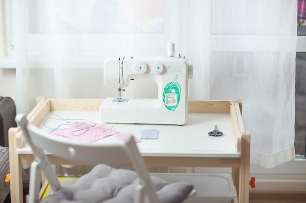 Come cucire maschera facciale, processo di cucitura maschera protettiva, pezzi di stoffa punteggiata, fili e macchina da cucire sul tavolo bianco con sedia bianca.