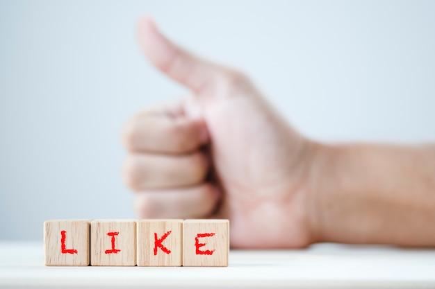 Come parola chiave sul cubo di legno e il pugno che mostra pollice su gesto