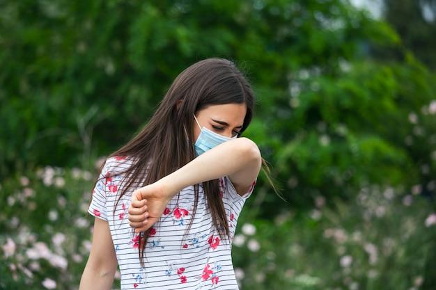 Come starnutire correttamente. donna con maschera protettiva starnutisce sul gomito. concetto di non diffusione del virus.