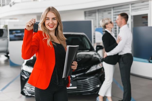 Commerciante di automobile che tiene una chiave che sta contro l'automobile. coppia in uno sfondo sfocato.