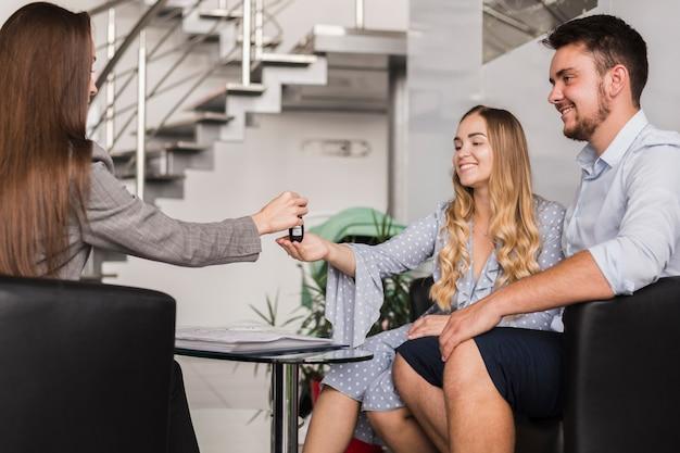 Commerciante di automobile femminile che fornisce le chiavi alle giovani coppie