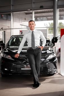 Commerciante di automobile maschio di angolo basso che si appoggia automobile