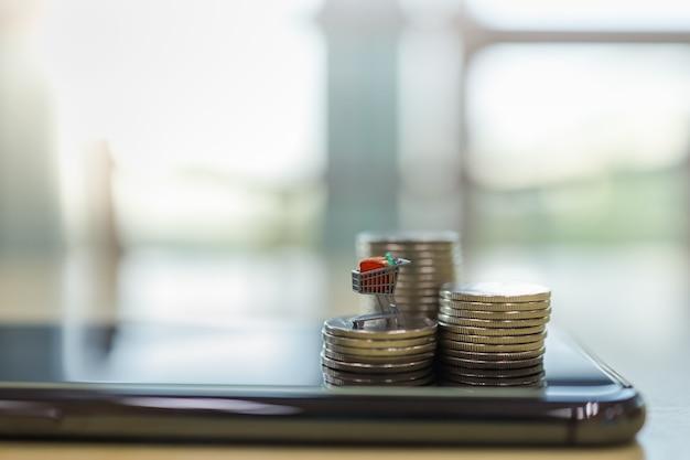 Commercio elettronico e concetto dei soldi. chiuda in su della figura miniatura del carrello o del carrello in cima alla pila di monete in cima sul telefono mobile astuto