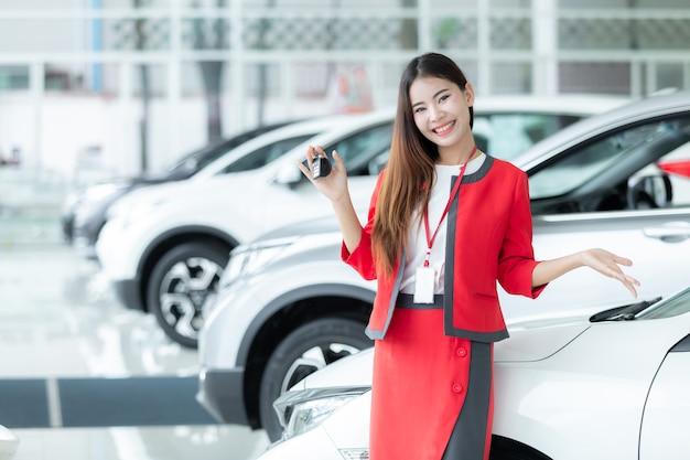 Commessa asiatica che fornisce chiave dell'automobile sopra il fondo di manifestazione automatica, affare automatico, vendita dell'automobile.