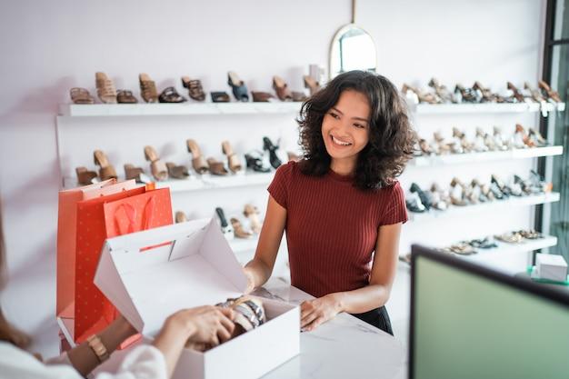 Commesso asiatico della donna con i contenitori di scarpe al deposito