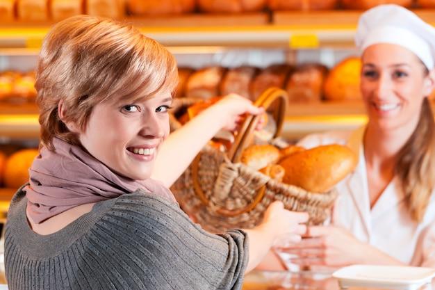 Commesso con cliente femminile in panetteria