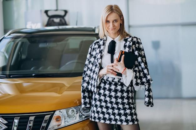 Commesso femminile in una sala d'esposizione dell'automobile che fa una pausa l'automobile