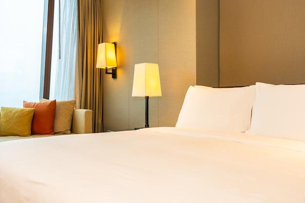 Comodo cuscino bianco e coperta sul letto con lampada
