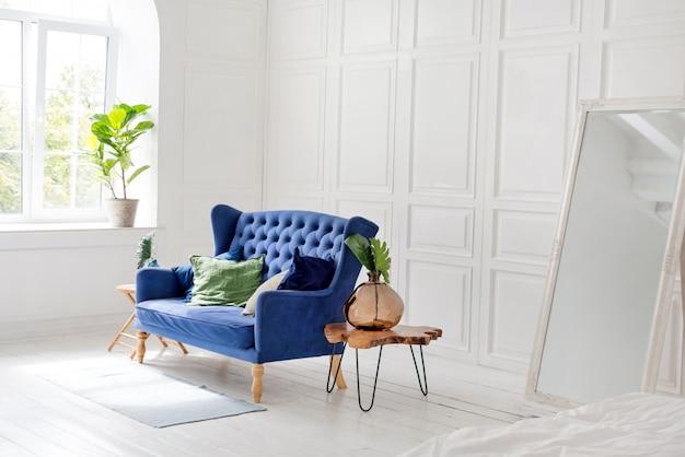 Comodo divano classico blu con cuscini e tavolino in legno in un semplice appartamento bianco