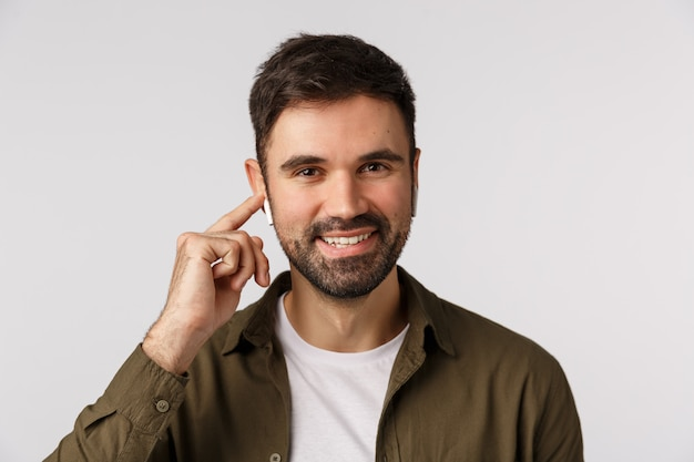 Comodo e facile da usare. attraente uomo moderno con la barba, uomo d'affari che cammina città e cliente ambulante tramite auricolari wireless, toccando le cuffie per cambiare volume o canzone nella playlist, sorridente