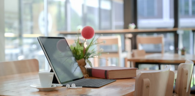 Comodo spazio di co-working con tablet con tastiera e libro, decorazioni e una tazza di caffè