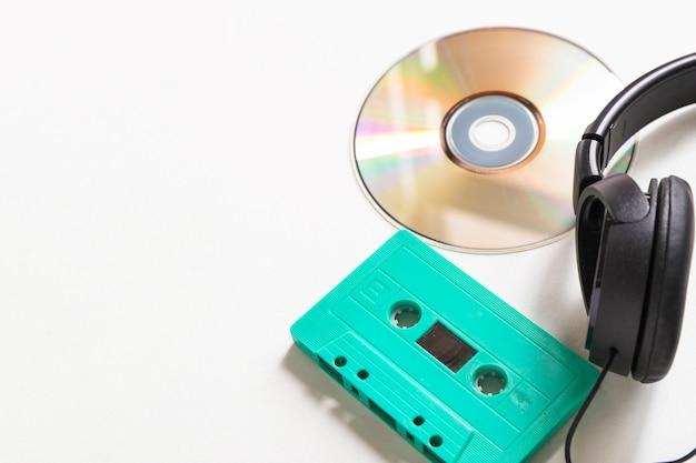 Compact disc; cassetta turchese e cuffie su sfondo bianco
